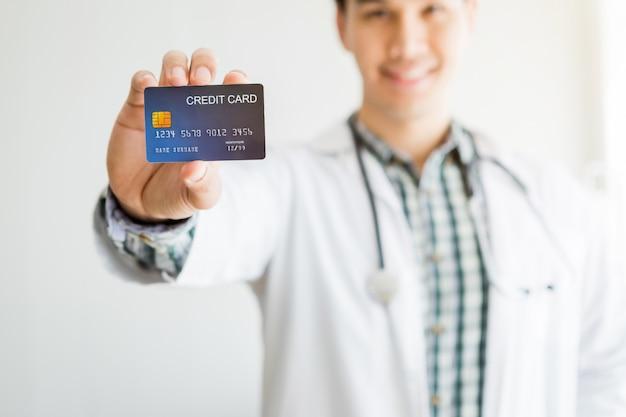Asiatische therapeutische ratende abstrakte unschärfe des doktors des jungen mannes mit der fokusshow, die eine kreditkarte auf bett im raumkrankenhaus, konzept der medizinischen behandlung der zahlung hält