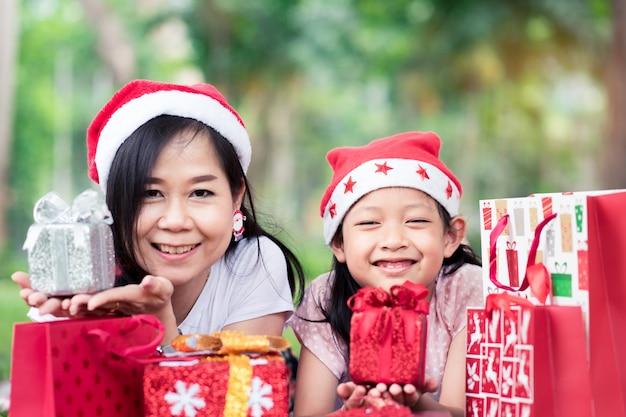 Asiatische tochter und mutter, die mit glücklichem in den frohen weihnachten lächelt