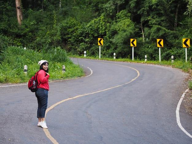 Asiatische touristenfrau, die auf kurvenreicher straße mit kurvenwarnzeichen im wald geht. hipster backpacker.