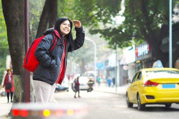 Asiatische touristenfrau, die auf pflaster steht und auf bus oder taxi wartet