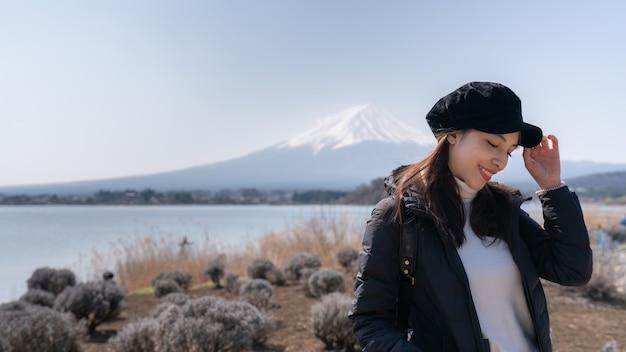 Asiatische touristenfrau fühlen sich auf dem gebiet des trockenen grases glücklich