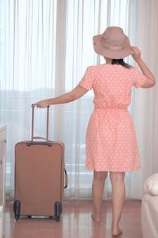 Asiatische touristenfrau in einem rosa kleid, die mit ihrem gepäck im hotelschlafzimmer steht, glücklicher frauenlebensstil mit feiertagssommerreise-ferienkonzept