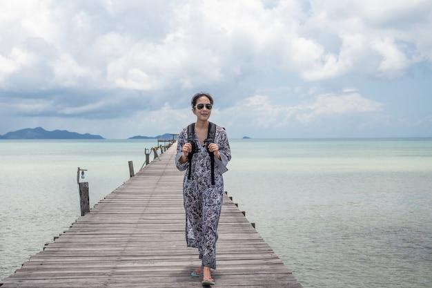 Asiatische touristenfrau in voller länge, die auf einer hölzernen brücke mit meerblick geht