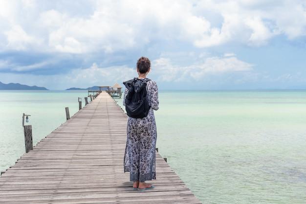 Asiatische touristin, die auf der hölzernen brücke steht und den ozean im urlaub betrachtet.