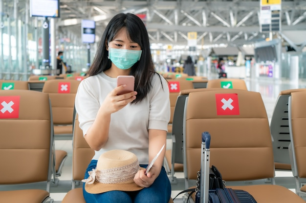 Asiatische touristin, die maske und soziale distanzierung im flughafenterminal trägt