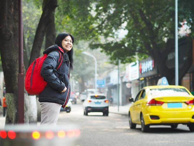 Asiatische touristische frau, die auf pflasterung steht und auf bus oder taxi wartet