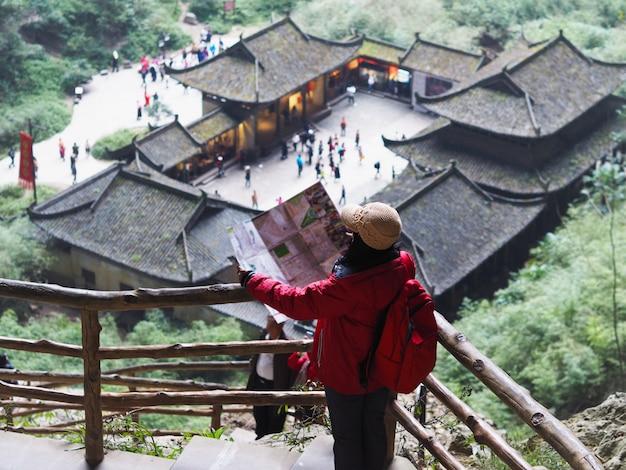 Asiatische touristische frau, die zur karte stadt in chongqing, china betrachtet.