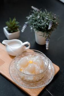 Asiatische traditionelle desserts sago mit kokosmilch auf schneidebrettern