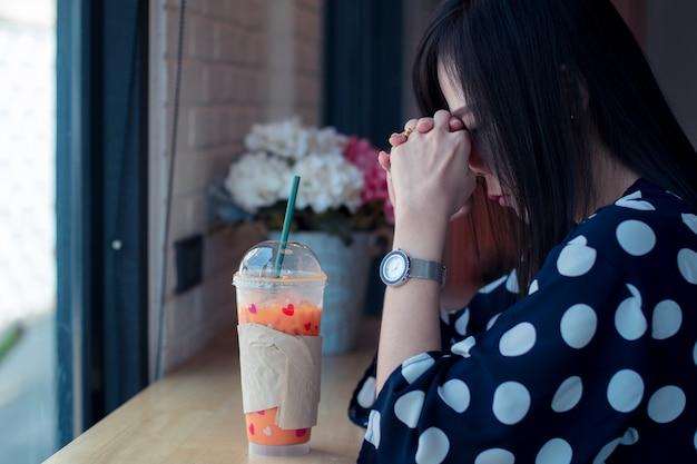 Asiatische traurige frau nahe fenster, das an etwas mit einsamkeit denkt
