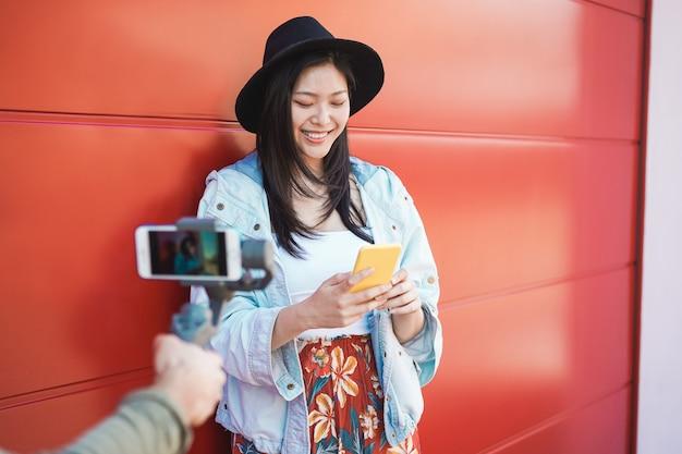 Asiatische trendige frau vlogging, während smartphone im freien verwendet wird. glückliches chinesisches mädchen, das spaß mit neuer trendtechnologie hat