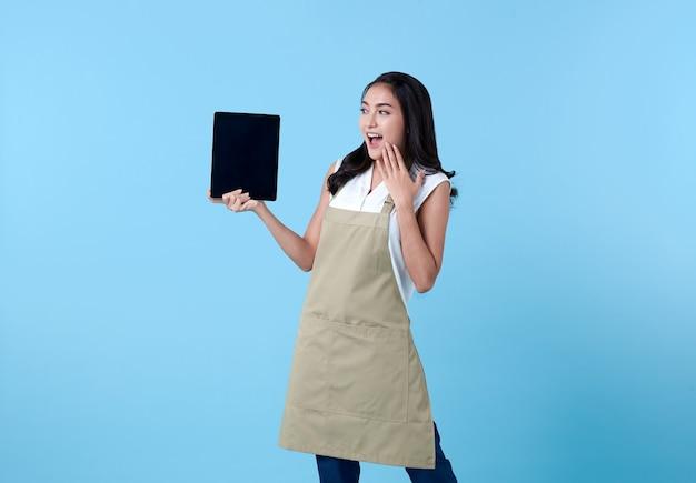 Asiatische unternehmerin, die tablet-computer auf blau verwendet.
