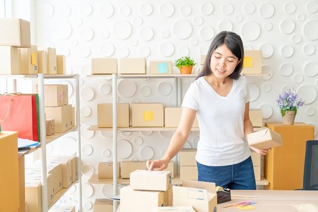 Asiatische unternehmerin, die zu hause mit verpackungsbox am arbeitsplatz arbeitet - online-shopping kmu-unternehmer oder freiberufliches arbeitskonzept