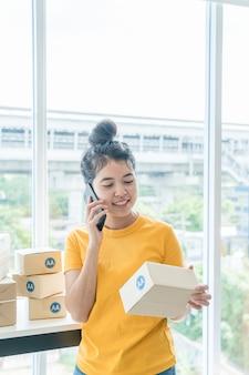 Asiatische unternehmerin, die zu hause mit verpackungsbox am arbeitsplatz arbeitet - online-shopping-kmu-unternehmer oder freiberufliches arbeitskonzept