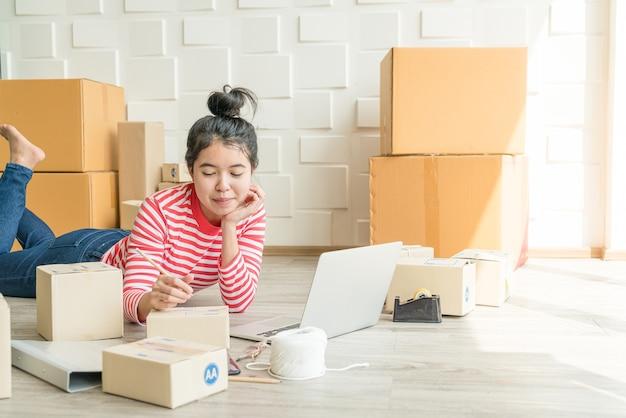 Asiatische unternehmerin, die zu hause mit verpackungsbox am arbeitsplatz arbeitet - online-shopping-kmu-unternehmer oder online-verkaufskonzept