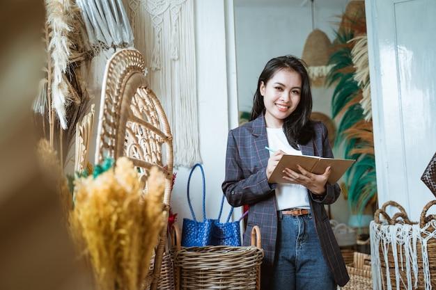 Asiatische unternehmerinnen machen sich notizen auf einem stand in einem kunsthandwerksladen auf einer handgemachten blume