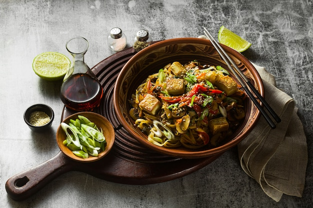 Asiatische vegane pfanne mit tofu, reisnudeln und gemüse, draufsicht.