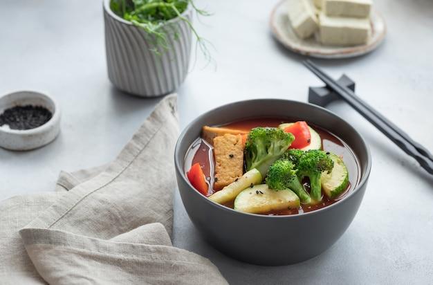 Asiatische vegane suppe mit tofu-käse und gemüse in dunkler schüssel pflanzenbasiertes lebensmittelkonzept