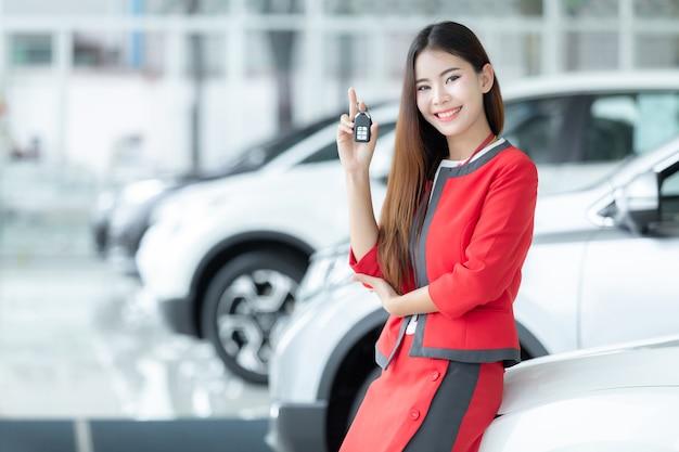 Asiatische verkäuferin, die autoschlüssel über autoshowhintergrund, selbstgeschäft, autoverkauf gibt.