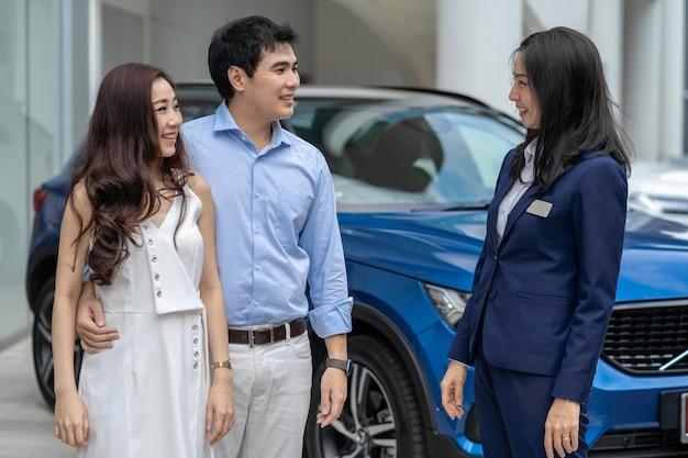 Asiatische verkäuferin, die den paarkunden zur prüfung des autos vor ausstellungsraum begrüßt