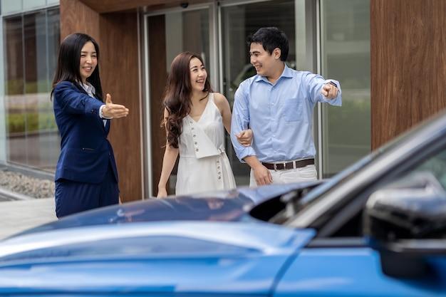 Asiatische verkäuferin, die den paarkunden zur prüfung des autos vor ausstellungsraum begrüßt,