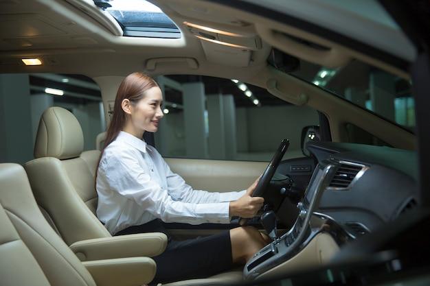 Asiatische verkäuferin im autogeschäft im auto