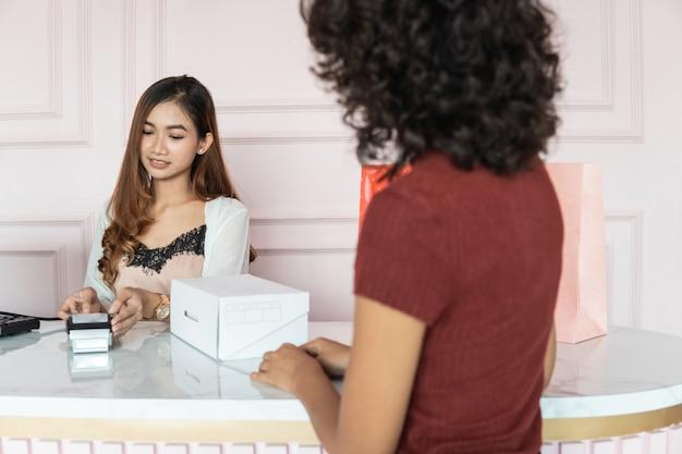 Asiatische verkäuferin mit schuhkartons im laden