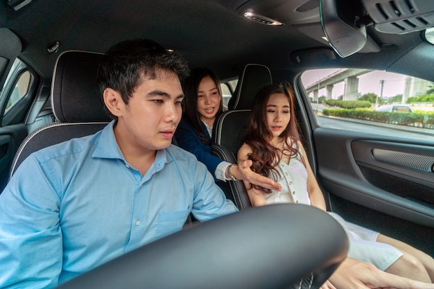 Asiatische verkäuferin riet der autofunktion, kunden für die prüfung des autos vor ausstellungsraum, service zu verbinden und konzept vorzustellen