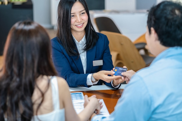 Asiatische verkäuferin, welche die kreditkarte vom paarkunden empfängt, wenn entscheidung das neue auto kauft