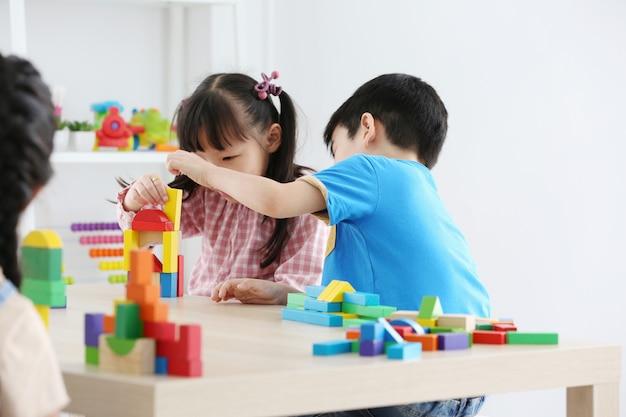 Asiatische vorschulstudentenbau-blockspielwaren zu hause oder kindertagesstätte. nettes kind, das mit farbwürfeln spielt. lernspielzeug für vorschul- und kindergartenkinder.