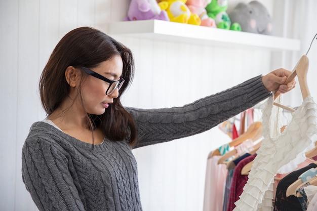 Asiatische wählende kleidung der hübschen frau und versuchende modekleidung mit spiegel zu hause schauen
