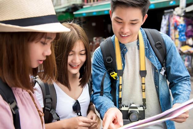 Asiatische wandererfreunde, welche die karte beim reisen in bangkok thailand betrachten