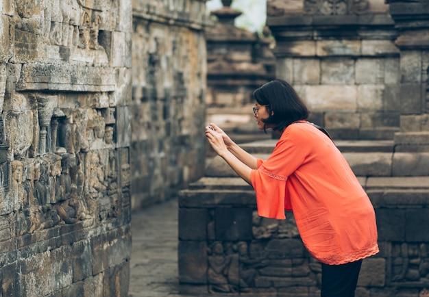 Asiatische weibliche alleinreisende benutzen smartphone machen alte gebäude des fotos an borobudur-tempel, java, indonesien