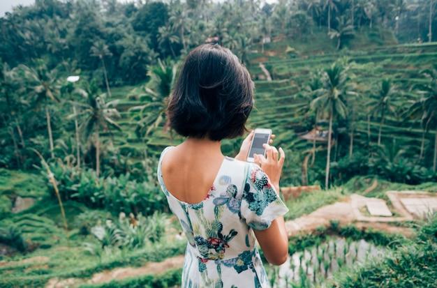 Asiatische weibliche alleinreisende benutzen smartphone machen foto tegalalang-reis-terrasse, ubud, bali, indonesien
