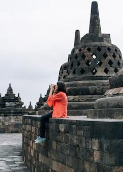 Asiatische weibliche alleinreisende machen alte gebäude des fotos an borobudur-tempel, java, indonesien