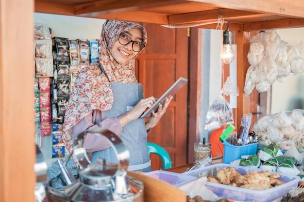 Asiatische weibliche angkringan-verkäuferin mit hijab und schürze unter verwendung eines tablet-pcs, der in der seite des wagenstandes steht