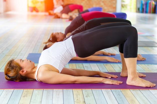 Asiatische weibliche gruppe der eignung, die namaste yogahaltung in der reihe an der yogaklasse tut. selektiver fokus