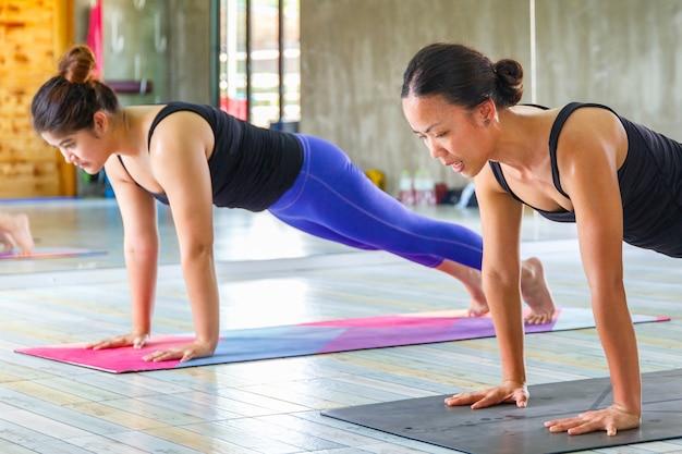 Asiatische weibliche gruppe der eignung, die namaste yogahaltung tut