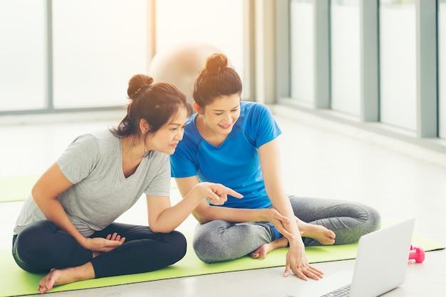 Asiatische weibliche zugfitness oder yoga online mit laptop, gesundes frauenlebensstilkonzept