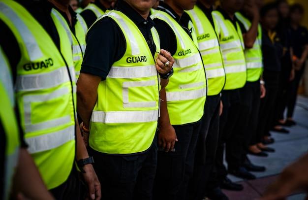 Asiatische wertpapiere und wachen stehen in der reihenversammlung und warten auf befehl des kommandanten der thailand-konzertveranstaltung.