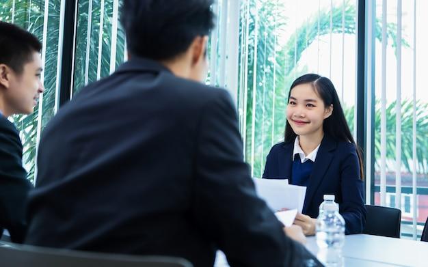 Asiatische wirtschaftler, die dokumente und ideen bei der sitzung besprechen