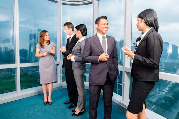 Asiatische wirtschaftler, die im büro sich treffen