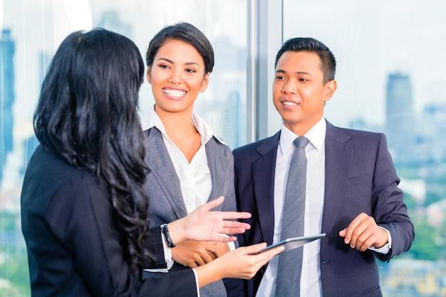 Asiatische wirtschaftler, die im büro stehen