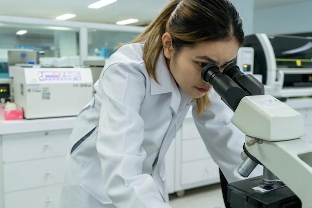 Asiatische wissenschaftler derzeit mit der maschine wissenschaftliche ausrüstung zum testen von blut aus dem reagenzglas.