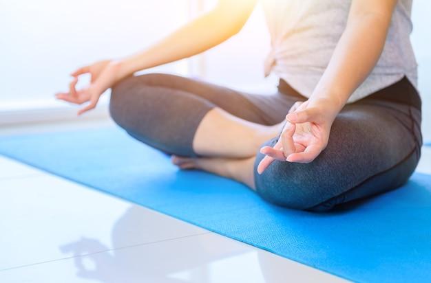 Asiatische yoga-atmung und meditation allein im fitness-studio. indoor-übungen und workouts für gesundheit und wohlbefinden.