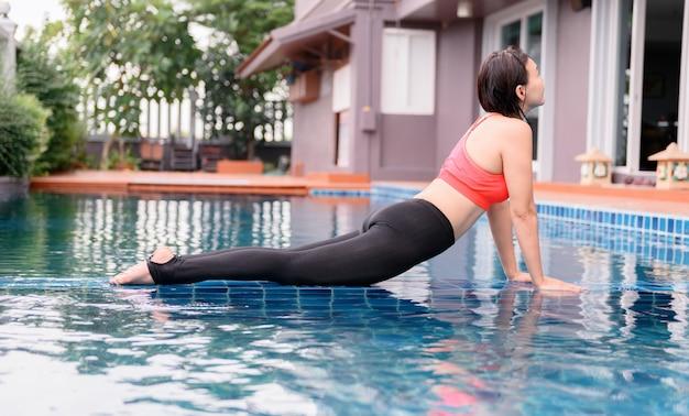 Asiatische yoga-atmung und meditation allein im schwimmbad zu hause. bewegung und training im freien für gesundheit und wohlbefinden.