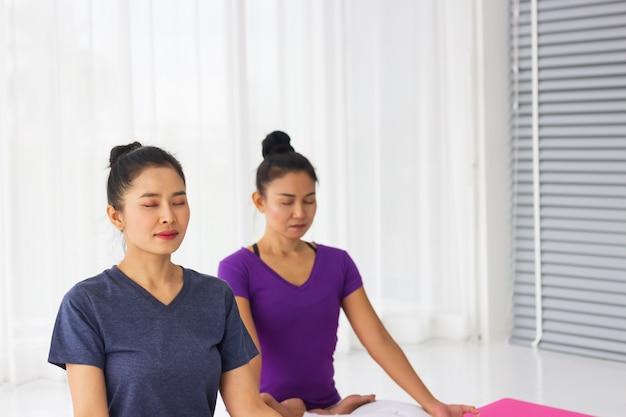 Asiatische yogalehrer bringen den schülern im fitnessstudio einzelunterricht bei, um gesund und stark zu sein.