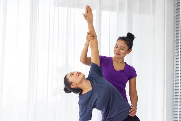 Asiatische yogalehrer unterrichten die schüler einzeln im fitnessstudio, gesund und stark zu sein.