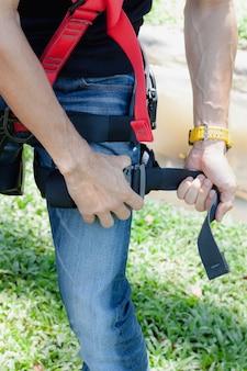Asiatischer abnutzungsabschluß des jungen mannes des nahaufnahmelosings das sicherheitsgurt für job in der höhe.