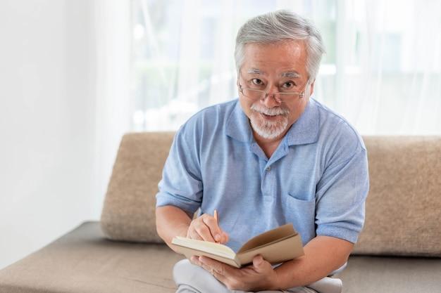 Asiatischer älterer alter mann mit brillenleseromanbuch, lächelndes gefühl glücklich auf dem sofa zu hause - lifestyle-konzept für ältere ältere menschen