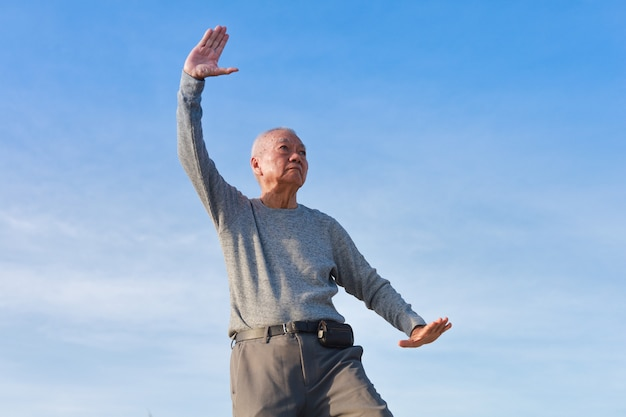 Asiatischer älterer alter mann üben taichi chinese kungfu am strand